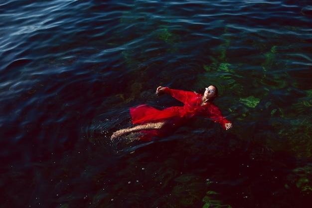 Vrouw zwemt in de zee in een rode lange jurk met zonnebril in de zomer