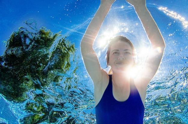 Vrouw zwemt onder water in zwembad, gezonde actieve meisje duikt en heeft plezier onder water, fitness en sport op vakantie op resort