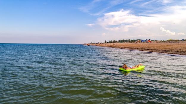 Vrouw zwemt op de zee op een matras die naar de zee kijkt
