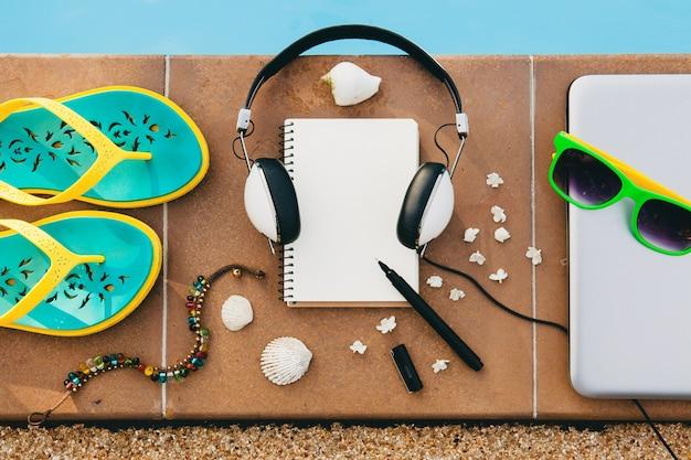 Vrouwaccessoires samengesteld op de vloer bij het zwembad, stilleven, uitzicht van bovenaf, zomermodetrend, vakantie, koptelefoon, notitieboekje, zonnebril, sandalen, zeeschelp, pen, reisdagboek, armband, bloemen