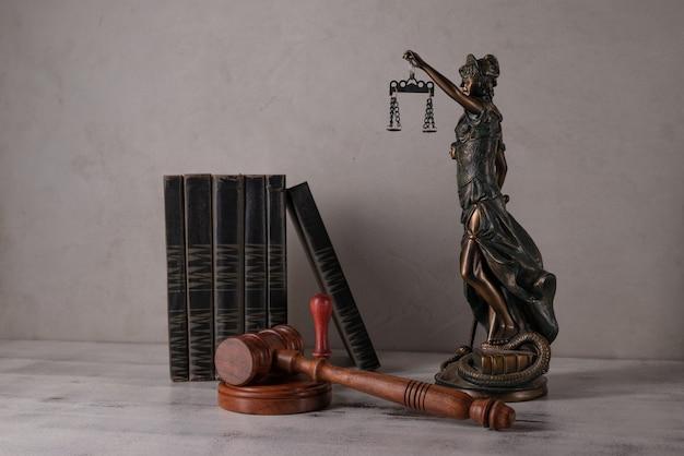 Vrouwe justitia, rechtershamer, boeken, perkamentrol met zegel en stempel op een oude houten tafel