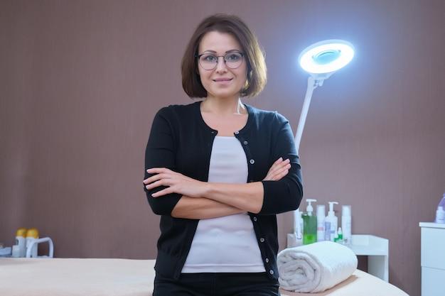 Vrouweigenaar van schoonheidssalon in de buurt van massagetafel en apparatuur