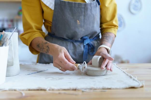 Vrouwelijk ambachtelijk werk met ruwe klei in aardewerkstudio, jong studentenmeisje bereidt materiaal voor op vormgeven