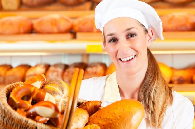 Vrouwelijk bakkers verkopend brood door mand in bakkerij