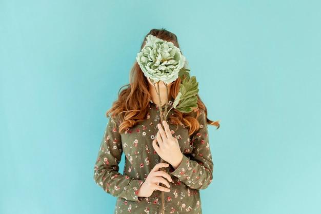 Vrouwelijk bedekkend gezicht met verse bloem