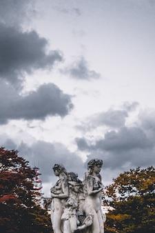 Vrouwelijk betonnen beeld onder witte wolken