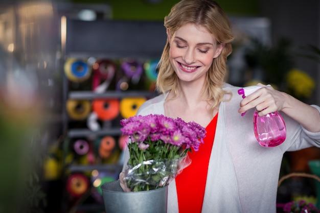 Vrouwelijk bloemist bespuitend water op bloemen in bloemenwinkel