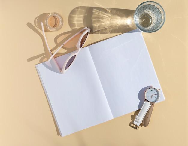 Vrouwelijk blogger-notitiesmodel. bovenaanzicht damesaccessoires, glas met water en geopende blanco blocnote. blanco vel papier met ruimte voor tekst