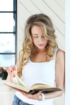 Vrouwelijk blond model dat een boek leest