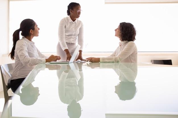 Vrouwelijk commercieel team dat project in conferentieruimte bespreekt