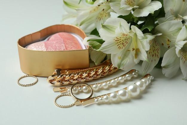 Vrouwelijk concept met juwelen en bloemen op wit