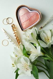 Vrouwelijk concept met juwelen en bloemen op witte achtergrond