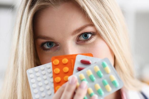 Vrouwelijk de holdingspak van de artsenhand verschillende tabletblaren bij werkplaatsclose-up. panacea life save service voorschrijven medicijn juridische drogisterij ziekte genezing bloeddruk concept