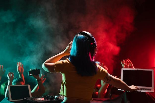 Vrouwelijk dj bij het mengen van console in club