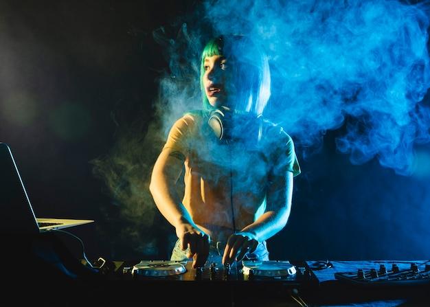 Vrouwelijk dj in club die door kleurrijke rook wordt behandeld