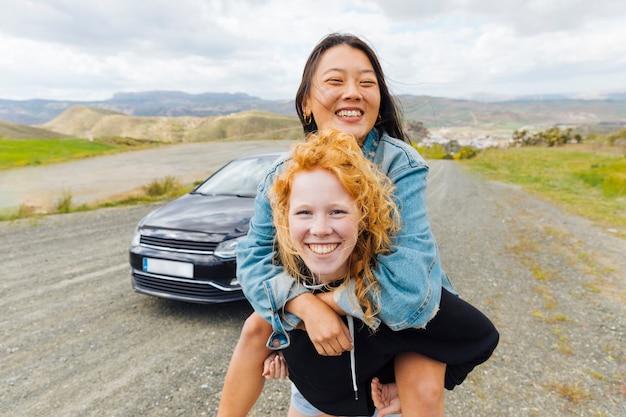 Vrouwelijk dragend meisje op rug op kant van de weg