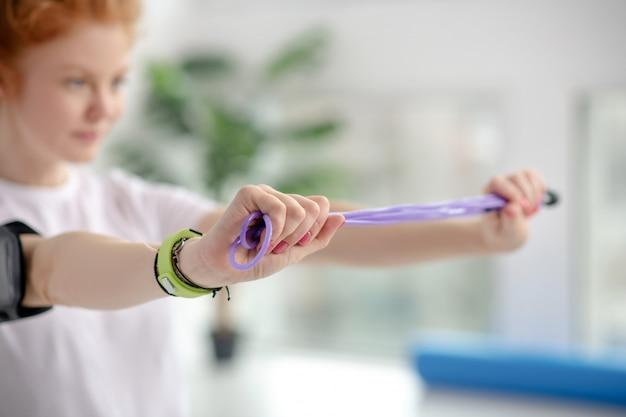 Vrouwelijk geduldig uitrekkend springtouw met handen