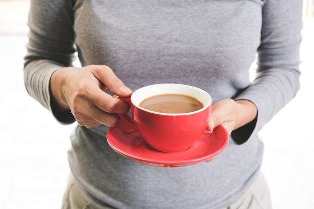 Vrouwelijk gen dat een rode koffiemok houdt