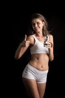 Vrouwelijk geschiktheidsmodel die een waterglas houden