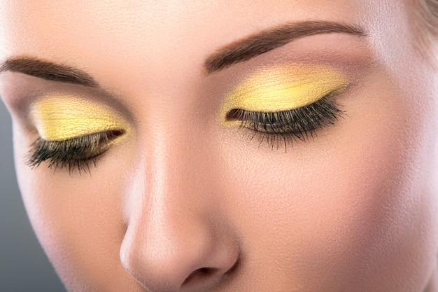 Vrouwelijk gezicht met gele oogschaduw