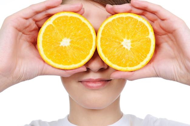 Vrouwelijk gezicht met verse sectiesinaasappel in plaats van haar ogen