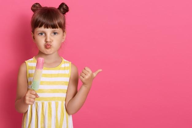 Vrouwelijk jong geitje die roomijs houden en opzij met duim richten, geïsoleerd stellen over roze muur, lippen rond houdend, ziet het kleine meisje zakelijk en grappig.