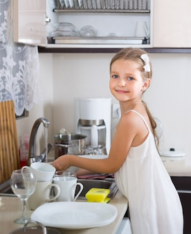 Vrouwelijk kind dat dishware thuis schoonmaakt