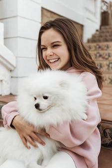 Vrouwelijk kind haar pluizige hond knuffelen