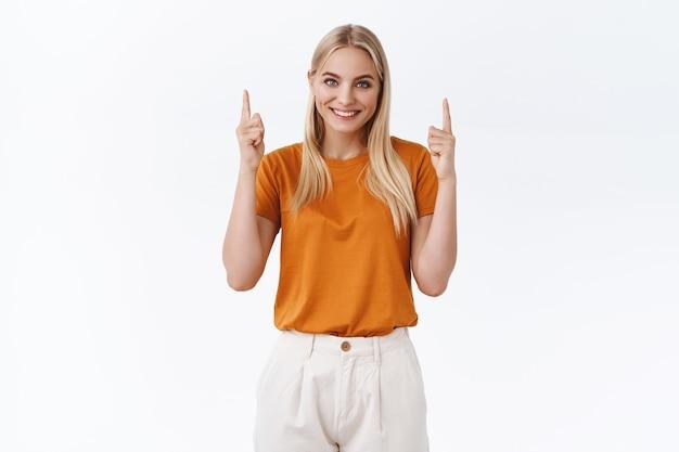 Vrouwelijk knap jong modern blond meisje in oranje t-shirt, broek die vingers opheft, omhoog wijst, vrolijk en zelfverzekerd glimlacht, advies geeft, geweldige plek suggereert, link, witte achtergrond staat