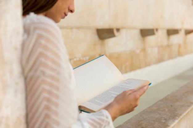 Vrouwelijk leesboek dichtbij de steenbouw