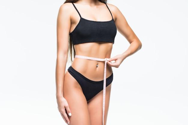 Vrouwelijk lichaam vrouw met centimeter tape rond op witte muur.