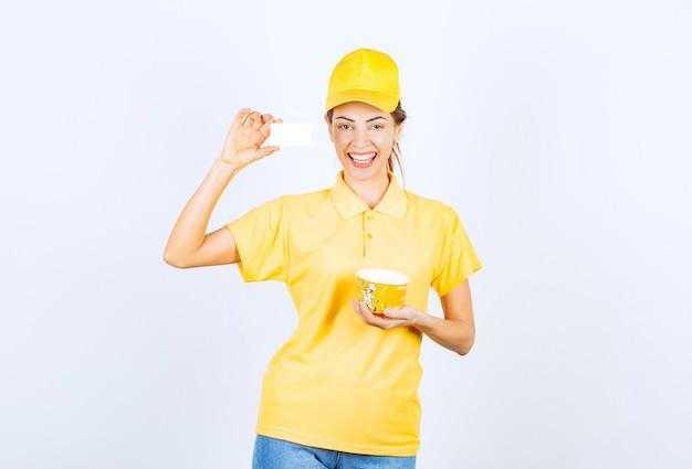 Vrouwelijk meisje in geel uniform levert een gele afhaalnoedelbeker en presenteert haar visitekaartje aan de klant.