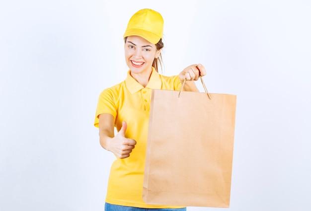 Vrouwelijk meisje in geel uniform met een kartonnen boodschappentas en duim opdagen.