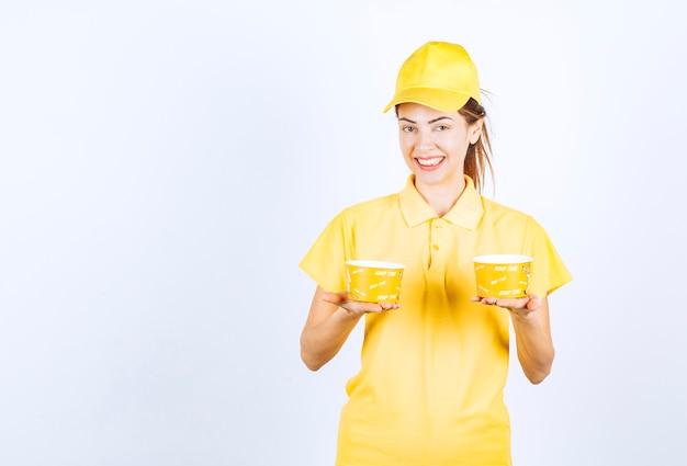 Vrouwelijk meisje in geel uniform met twee meeneemnoedelbekers.