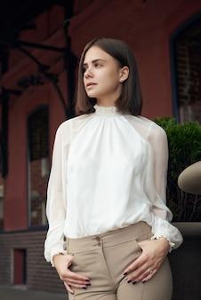 Vrouwelijk modeconcept. outdoor taille portret van jonge mooie vrouw die zich voordeed op oude straat.