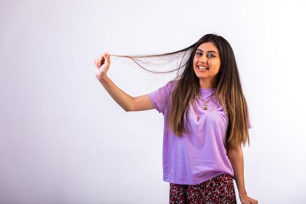 Vrouwelijk model dat haar hand op haar haar legt en pret heeft.