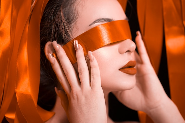 Vrouwelijk model dat haar ogen met rood lint sluit