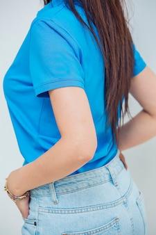 Vrouwelijk model dat jeans en t-shirt voor online verkoop promoot.