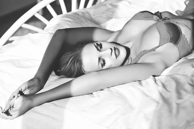 Vrouwelijk model dat lingerie op bed in de ochtend draagt