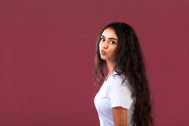 Vrouwelijk model gieten in de cosmetica van de herfstwinter commercieel op rode muur.