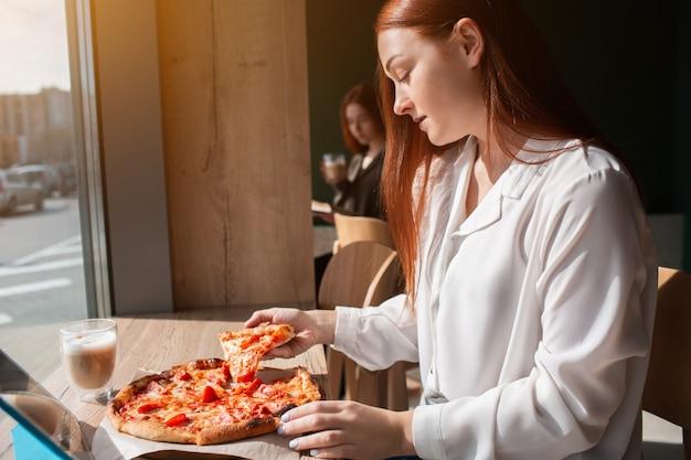 Vrouwelijk model houdt een stuk pizza in haar handen. jonge vrouw die pizza eet.