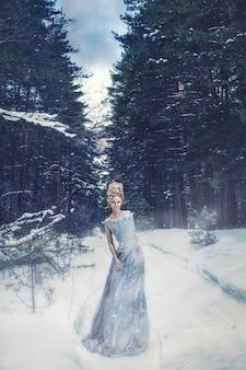 Vrouwelijk model in de afbeelding van de sneeuwkoningin met het juiste haar en make-up in het winterbos