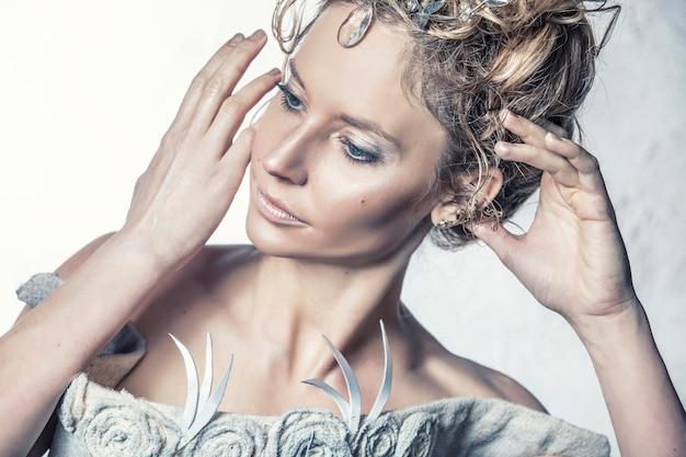 Vrouwelijk model in de afbeelding van de sneeuwkoningin met het juiste haar en make-up in studio