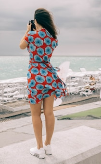 Vrouwelijk model in een jurk die de zee filmt