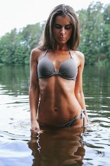 Vrouwelijk model in grijze zwembroek in het meer