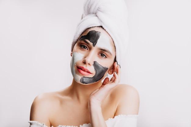 Vrouwelijk model in handdoek na het wassen van haar hoofd. het meisje geeft procedures voor gezicht.