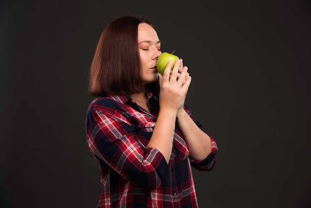 Vrouwelijk model in herfst-wintercollectie-outfits die een groene appel vasthouden en eraan ruiken.