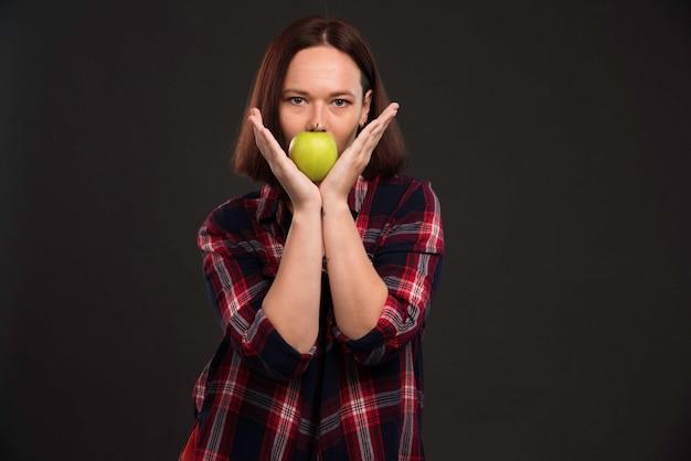 Vrouwelijk model in herfst wintercollectie outfits met een groene appel op haar mond.