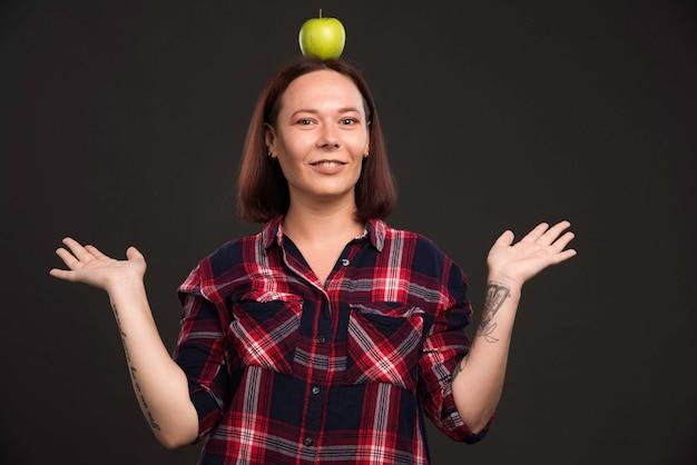 Vrouwelijk model in herfst wintercollectie outfits met een groene appel op het hoofd.