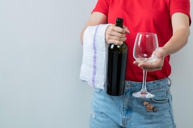 Vrouwelijk model in rood overhemd dat een fles wijn met glas houdt.